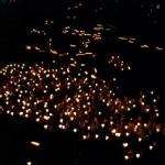 Bedevaartgangers met kaarsen in Lourdes