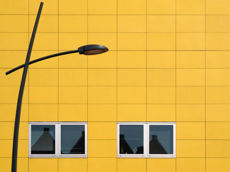 Lantaarnpaal tegen gele gevel