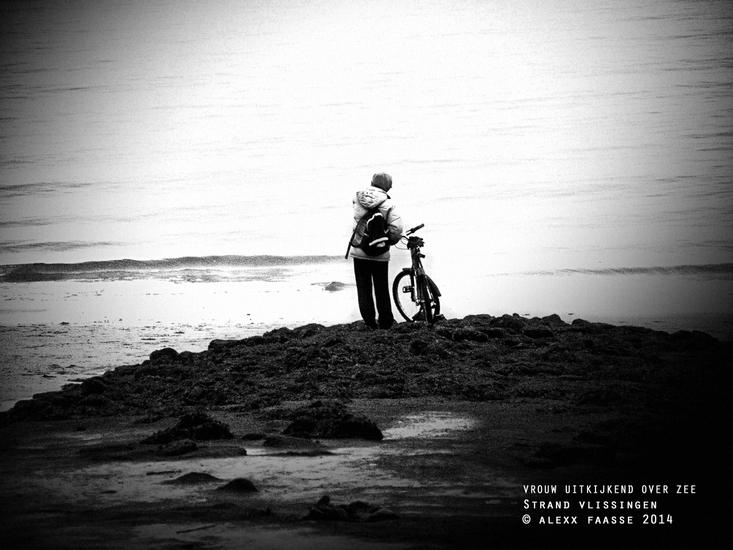 Vrouw tuurt over de zee